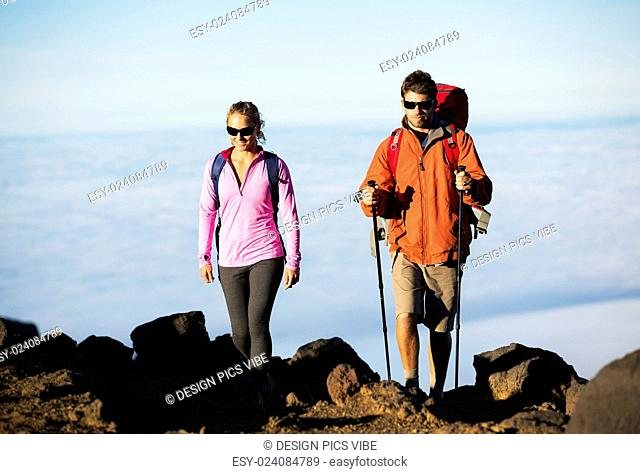 Hiking in the mountains. Happy athletic couple with backpacks enjoying hike outdoors on beautiful mountain trail