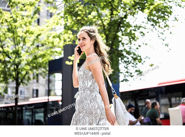 Smiling woman on cell phone in the city on the go