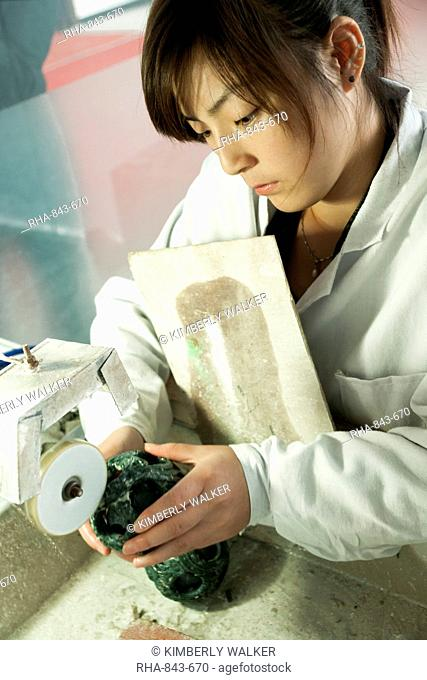 Asian woman polishes jade over a sink in a Jade Factory, Shanghai, China, Asia