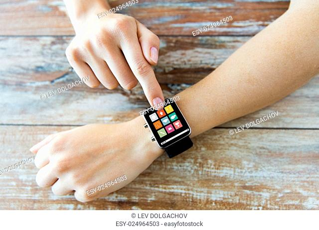 business, modern technology, media and people concept - close up of female hands setting smart watch with menu icons on screen on wooden table