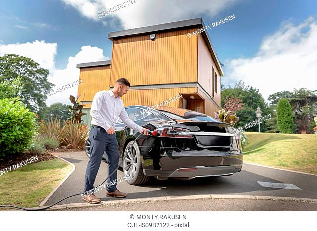 Man charging electric car outside modern house