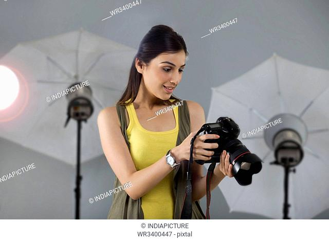 Beautiful young female photographer looking into digital camera