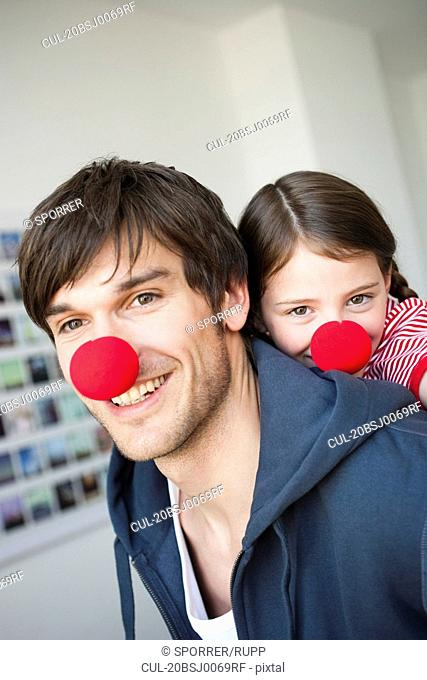 Father and girl with red noses