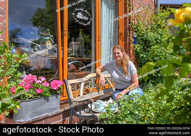 27 May 2020, Brandenburg, Biesenthal: Pamela John, operator of the Imperial Post Office, is sitting in the small garden in front of her building
