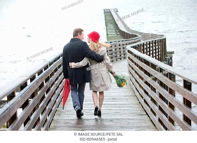 Couple walking on wooden dock