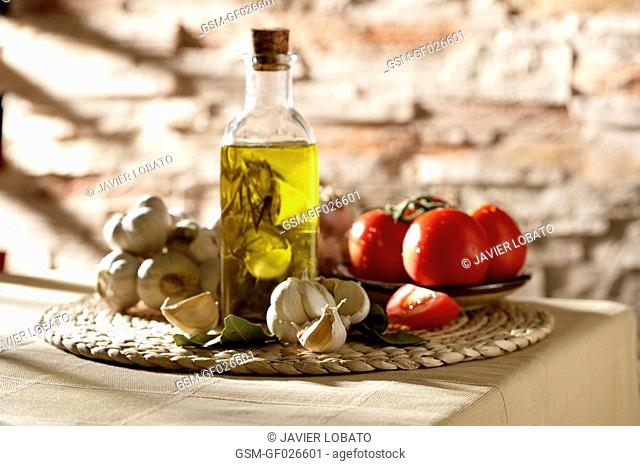 Mediterranean still life with natural light, tomatoes, olive oil, bay leaves and garlic