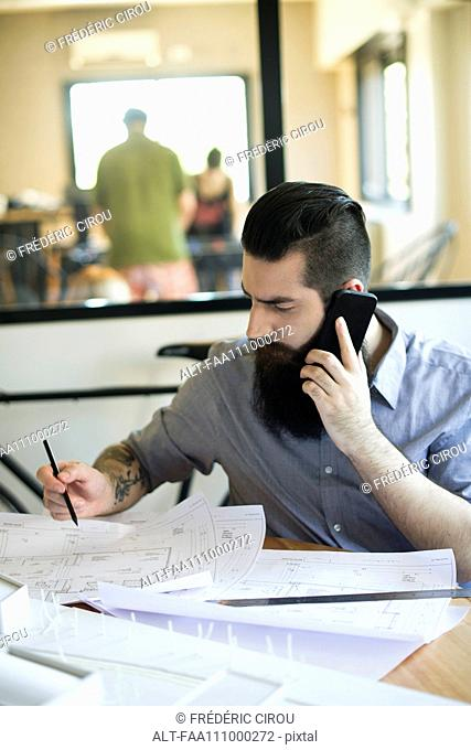 Man talking on cell phone and looking at blueprints in office