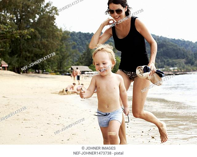 Mother running with son on beach