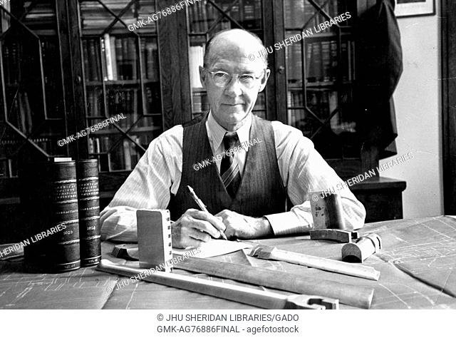 Professor of engineering at Johns Hopkins University Alexander Graham Christie sitting at his desk with a book shelf behind him, Baltimore, Maryland, 1950
