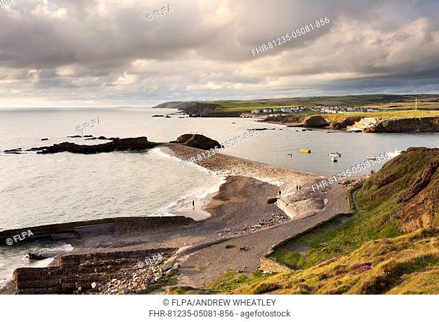View of coastline with beach and breakwater during high tide under stormclouds in late evening, Summerleaze, Bude, Cornwall, England, August