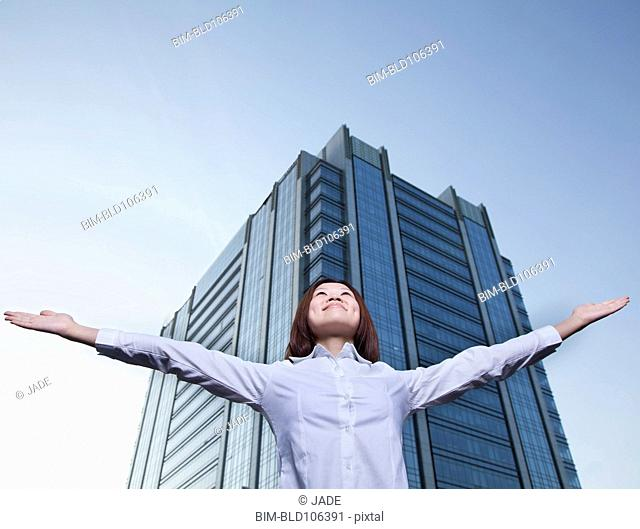 Chinese businesswoman with arms outstretched