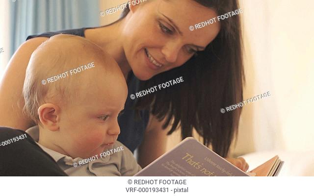 Mother and 12 month old baby reading on bed indoors