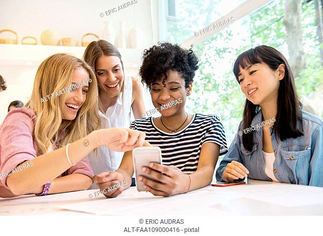 Friends looking at multimedia smartphone together in cafe