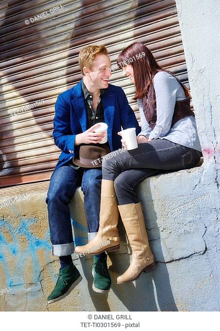 USA, New Jersey, Jersey City, young couple sitting on wall