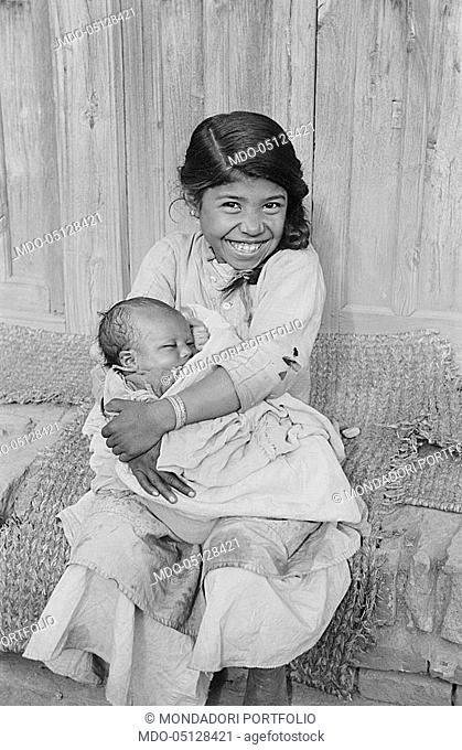 Smiling Nepalese girl holding a baby. Nepal, 1965