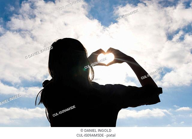 Silhouetted mid adult woman making heart shape with hands in front of blue sky
