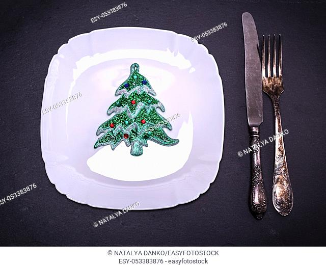 white square plate with Christmas decorations near iron cutlery on black background, top view