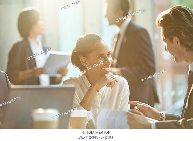 Smiling business people discussing paperwork in meeting