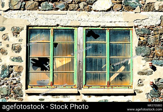 Closed metal windows on a stoned wall with broken glass from an abandoned building