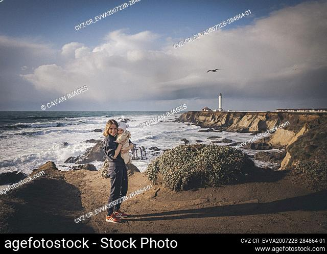 A woman is holding a baby near a lighthouse on the pacific coast