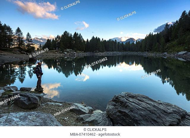Hiker on the shore of Lago Azzurro, Spluga Valley, province of Sondrio, Valtellina, Lombardy, Italy