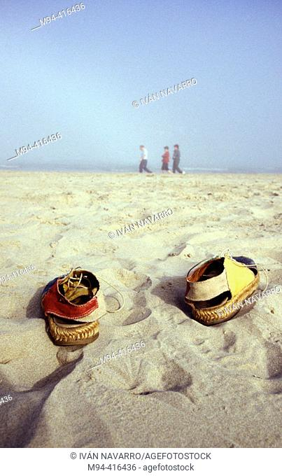 Esparto sandals on the beach. People strolling in background