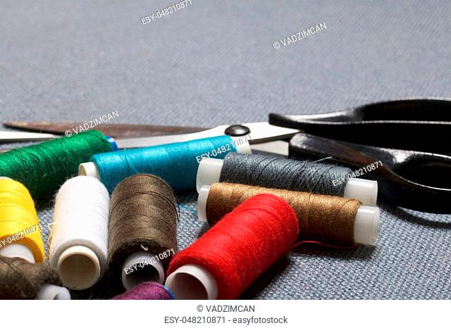 Coils of thread of different colors on a gray fabric background and scissors