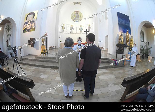 09 May 2021, Bavaria, Munich: Vicar Wolfgang Rothe blesses a man and a woman during a Catholic service with the blessing of homosexual couples as part of a...