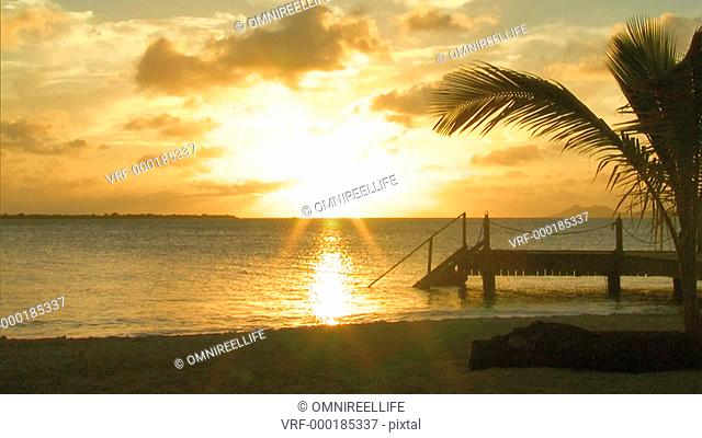 Sun setting through clouds on sea's horizon with palm trees and jetty in foreground