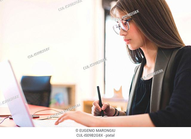 Young woman at office desk using laptop