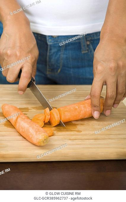 Mid section view of a woman cutting a carrot