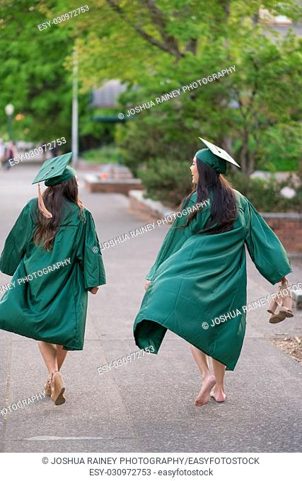 Two female college students walking together towards graduation ceremonies on a university campus during the Spring in Oregon