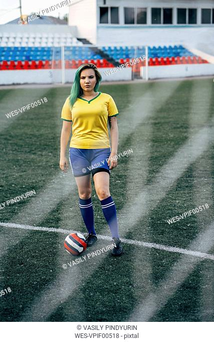 Young woman standing on football ground with the ball