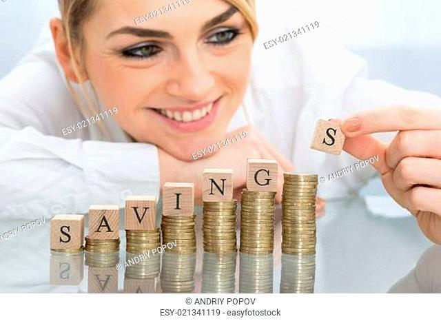 Close-up Of Young Businesswoman With Savings Blocks On Golden Stacked Coins