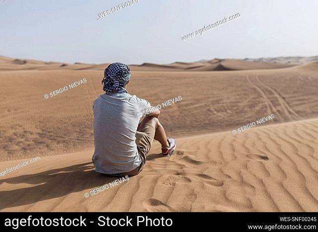 Male tourist sitting on sand dunes in desert at Dubai, United Arab Emirates