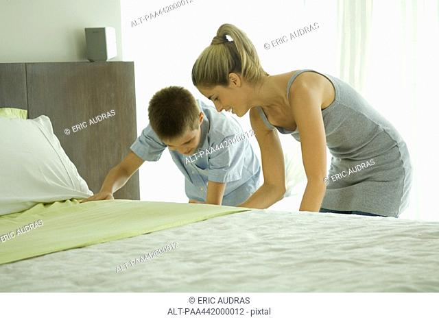 Mother and son making bed together