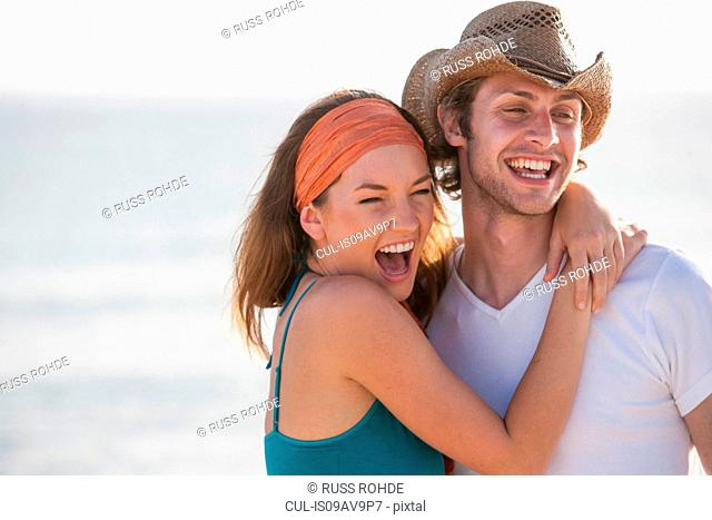 Portrait of happy young couple hugging at seaside