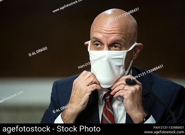 Stephen Hahn, Commissioner, United States Food and Drug Administration (FDA), adjusts a face covering during a Senate Health, Education