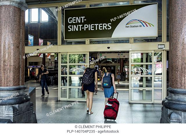 Travellers with backpacks at the entrance of the Gent-Sint-Pieters / Saint Peter's railway station in Ghent, East Flanders, Belgium