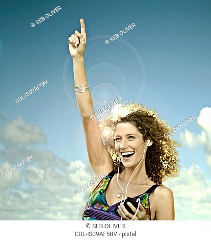 Young woman listening to MP3 player dancing outdoors