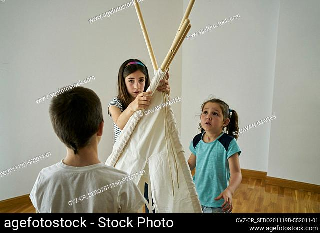 Children putting the sticks to build a teepee tent inside their house. Creativity concept