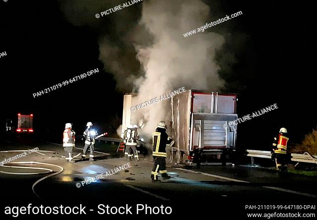 19 October 2021, Lower Saxony, Melle: Firefighters extinguish a burning trailer of a truck on the Autobahn 30 near Melle (Osnabrück district)