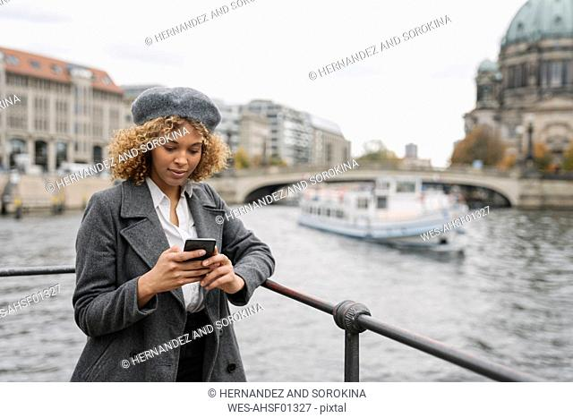 Tourist woman using smartphone in the city with Berlin Cathedral in background, Berlin, Germany