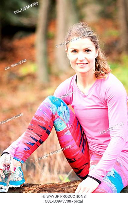 Young woman wearing sportswear, sitting with leg raised, looking at camera smiling