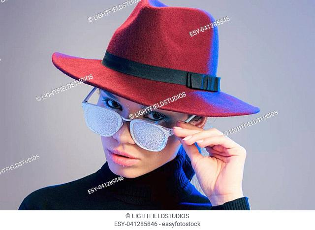 Young good-looking woman wearing wide-brimmed hat, looking at camera over sunglasses covered in frost