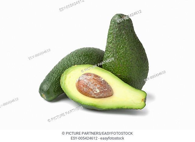 Whole and half fresh avocados on white background