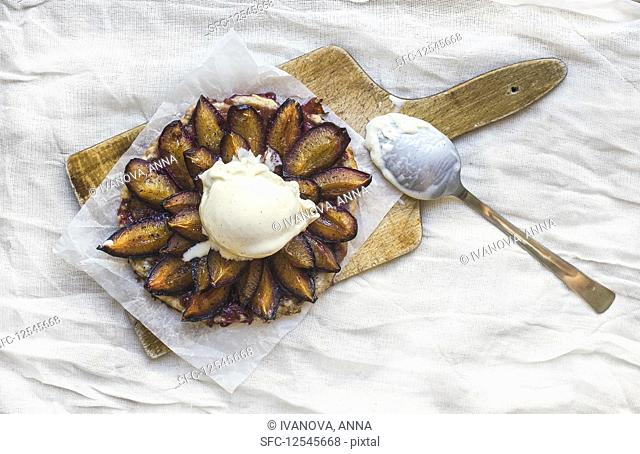 Plum pie with vanilla ice-cream ball on a wooden board over a piece of white rough tissue