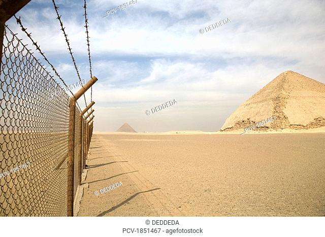 A barbed wire fence by the Bent Pyramid with Pyramid of Giza in background