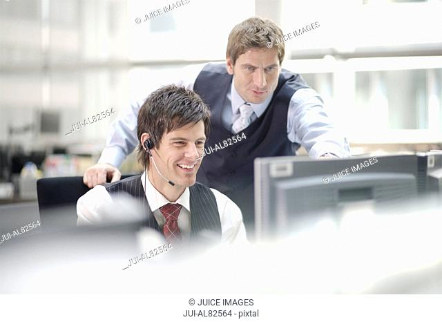 Two businessmen looking at computer monitor
