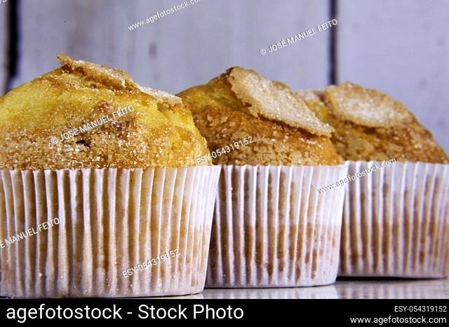 three delicious cupcakes close-up in line on wooden background